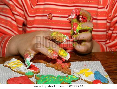 A young girl fingerpainting ginger bread cookies for christmas