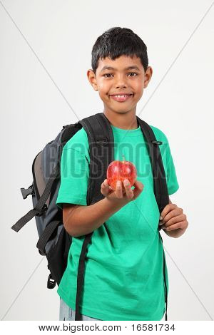 Cheerful school boy 10 smiling holding red apple