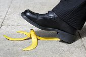 foto of differential  - Businessman about to slip and fall on a banana skin - JPG