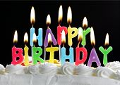 stock photo of happy birthday  - Colorful happy birthday candles burning on a cake - JPG