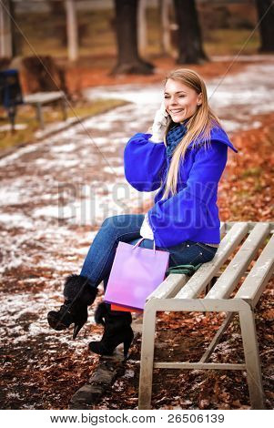 The happy young girl sitting on a bench in park