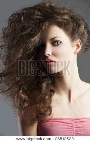 Menina bonita com o estilo de cabelo grande, ela é retratada a meio busto