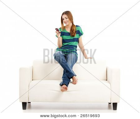 Beautiful young woman sitting on a sofa and sending a text message