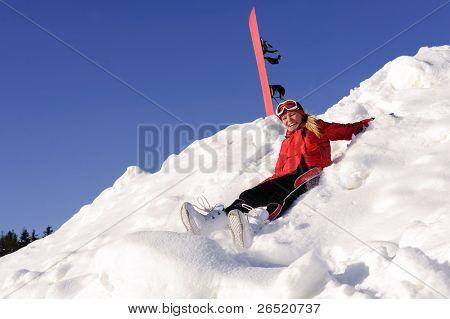 glücklich aktive junge Frau sitzen im Schnee nach springen