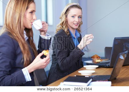 Two businesswoman sitting at conference table have a break during meeting