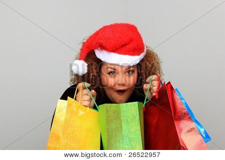 Beautiful young woman wearing a Santa hat and holding shopping bags over neutral background