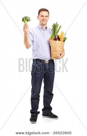 Full length portrait of a young man holding a shopping bag with products and a broccoli in his hand isolated on white background