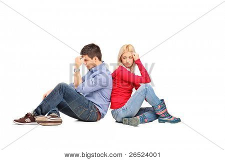 Couple sitting with their backs turned after having an argument isolated on white background