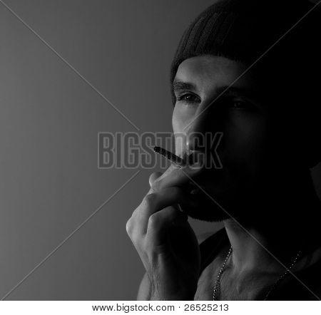 Solitario hombre joven con un cigarrillo en la oscuridad