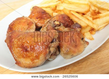 A serving dish piled with roast lemon chicken thighs and French fries, or chips, with a serving spoon
