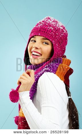 Photo of happy woman in knitted winter cap and scarf posing before camera