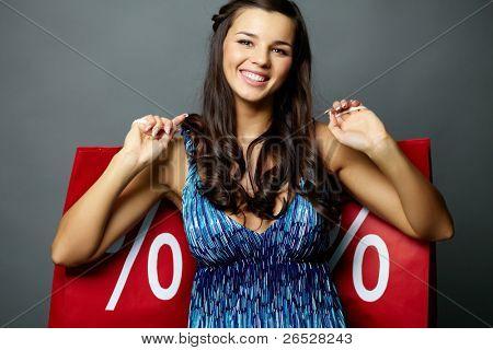 Retrato de uma morena sorridente com venda paperbags olhando para câmera