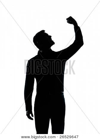 one caucasian business man angry fisting up  portrait silhouette in studio isolated on white background