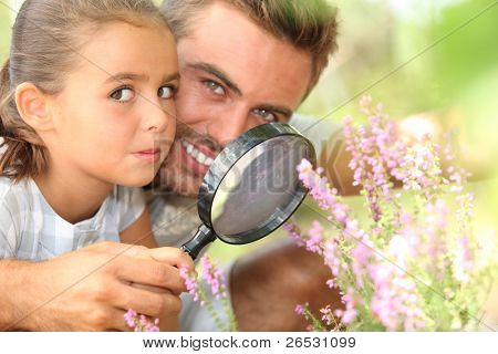 father and little daughter observing flowers with magnifying glass