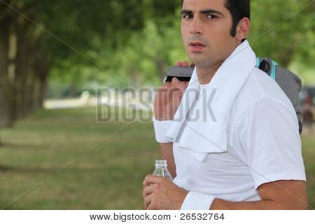 Sportsman in a park with a bottle of water