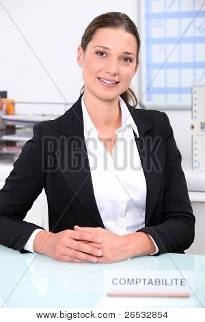 Smart female accountant sitting at her desk
