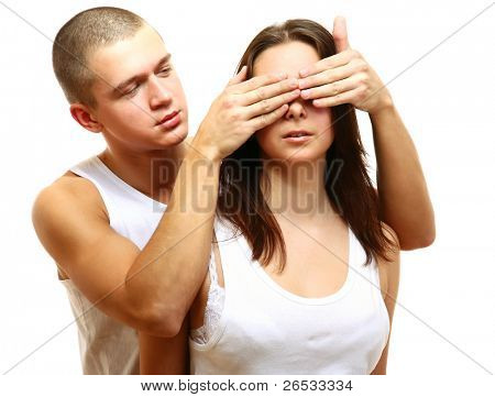 Young couple isolated. Young man covers his girfriend's eyes isolated
