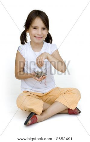 Little Girl Putting Money Into The Piggy Bank