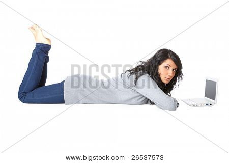 Portrait of beautiful young girl laying on the floor using a laptop over white background. Isolated