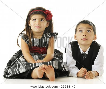 Two young children on the floor in party clothes with their eyes looking up.  On a white background.