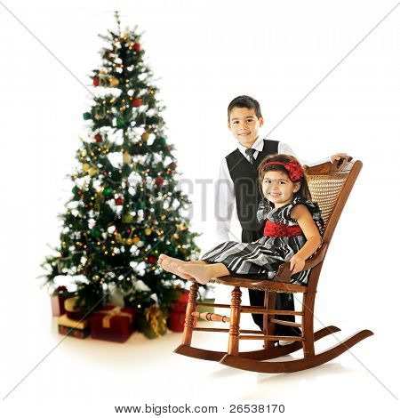 Dressed-up siblings posing near a Christmas tree in an old rocking chair.  On a white background.