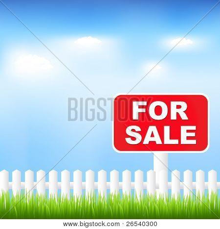 Sinal de venda com a grama e o céu azul