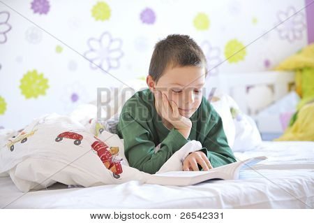 Young boy in his bed reading a book