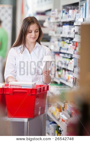 Female pharmacist in drugstore stocking shelves