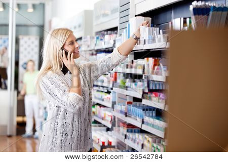 Female talking on cell phone while looking for medicines at drugstore