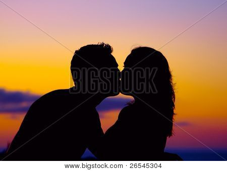 Silhouette of couple kissing at sunset
