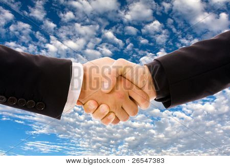 Business men hand shake over a blue sky with clouds as background