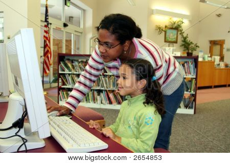 Child On Computer With Teacher