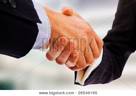 Business handshake between office bulding