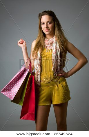 Beautiful young woman holding shopping bags against a grey background