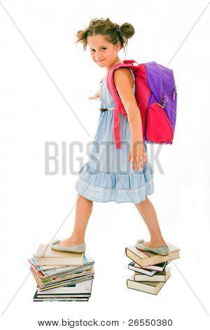 Retrato de muchacha litle con mochila caminando de tapa a tapa de pilas de libros