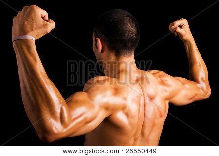 Retrato de un fuerte detrás de un joven musculoso sobre fondo oscuro
