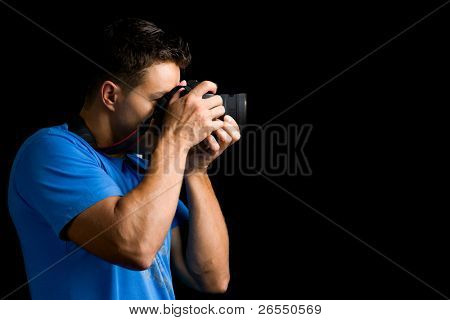Young photographer with camera against black background