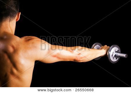 Back view of a young male bodybuilder doing heavy weight exercise with dumbbells against dark background