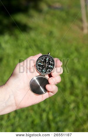 Granny Hands With Compass On Green Lawn