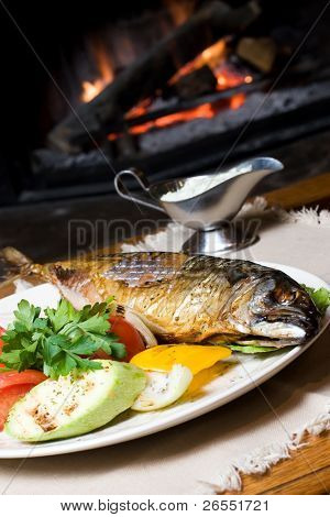 A fish dinner on a plate with vegetables in front of a fire