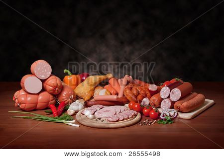 sausage. A variety of processed cold meat products, on a wooden cutting board.