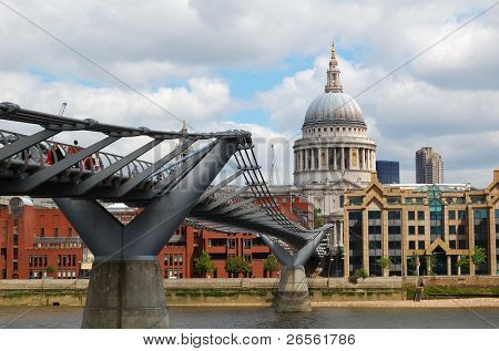 View of St Paul Cathedral and the Millennium Bridge with a cloudy sky