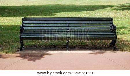 A green wooden bench with iron legs in the grass