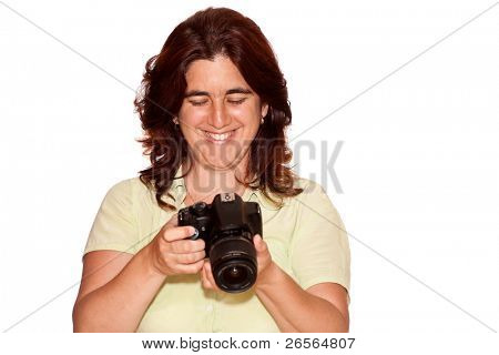 Beautiful woman looking at the pictures taken on a professional camera on a white background