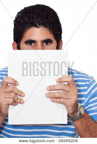 Young latin man hiding behind a book useful as copyspace isolated on a white background
