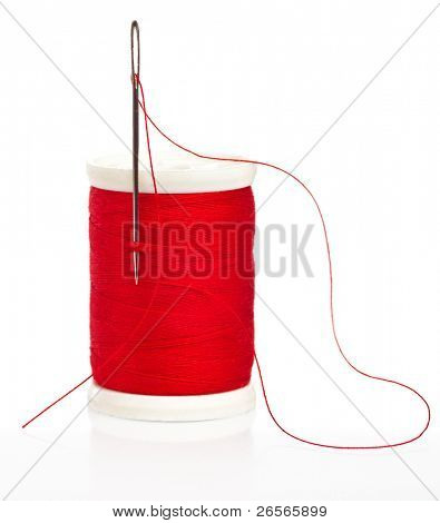 Reel with thread and needle on a white background