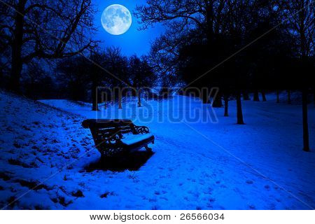 Bench in a park covered in snow at midnight with a bright full moon