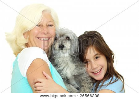 Grandmother and girl hugging the family dog isolated on a white background