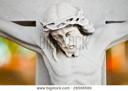Marble statue of the crucifixion of Jesus with a colorful out of focus background