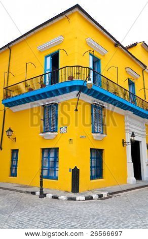 Typical bright yellow house with blue doors and windows in a corner in old Havana isolated on white